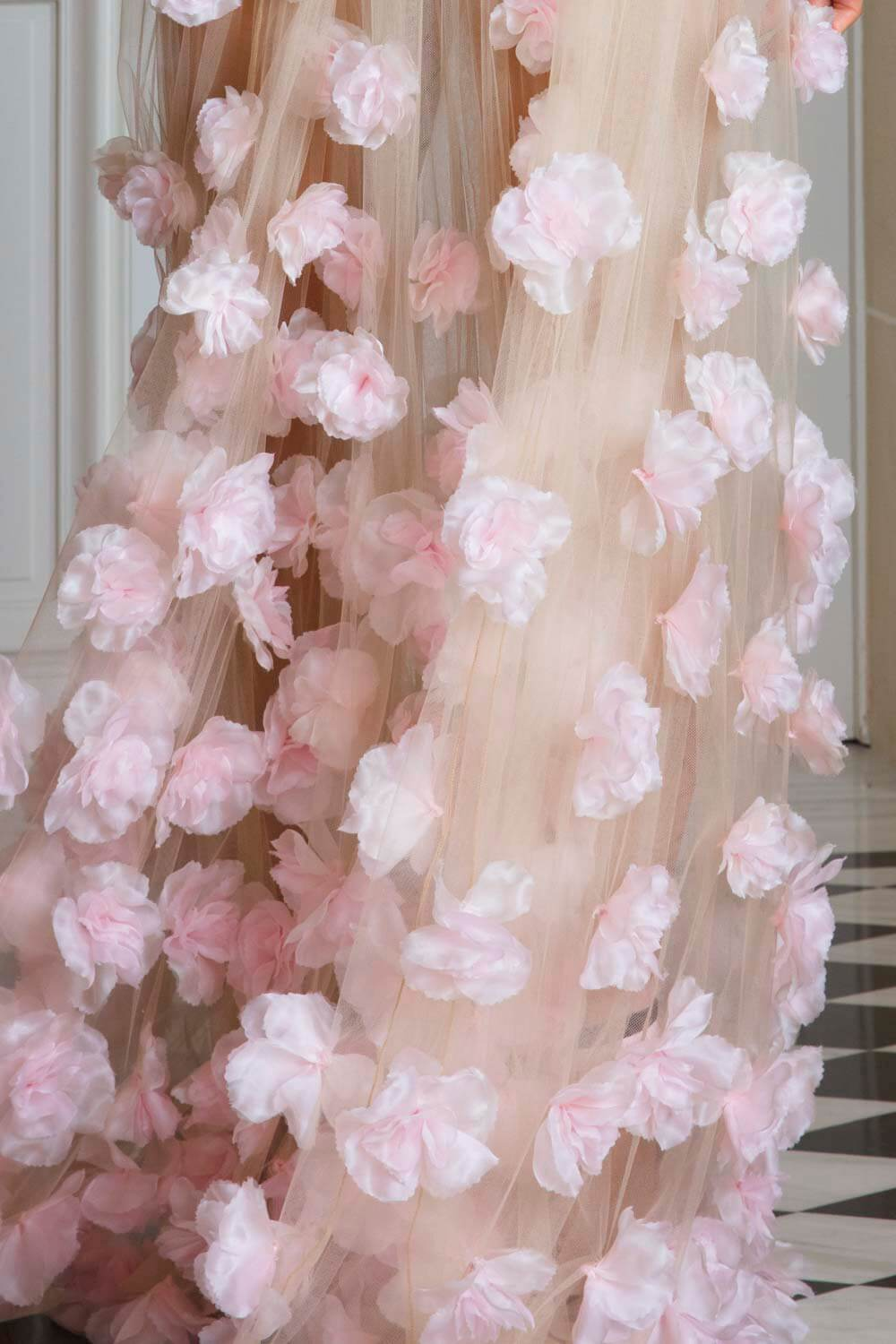 Barely-there nude floor-length gown with pink appliqué petals, worn over a fitted nude body